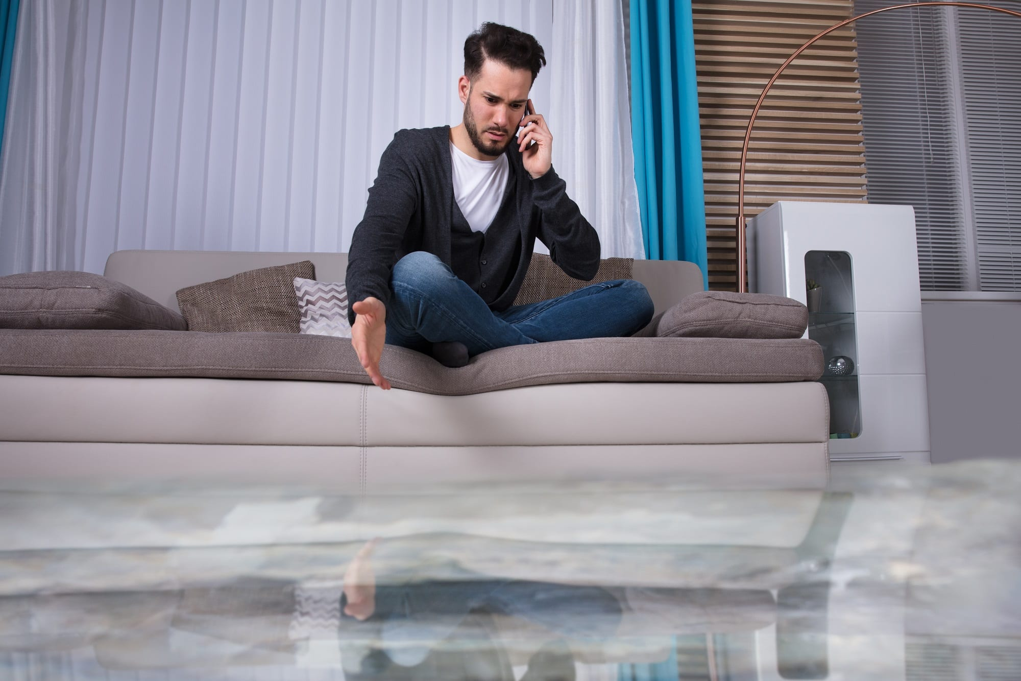 Man Sitting On Sofa Calling To Plumber